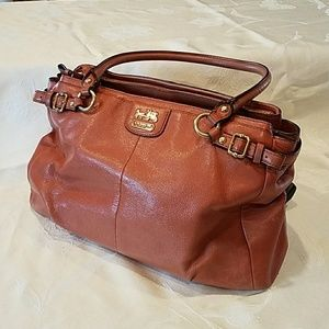 Camel colored COACH handbag with red lining.